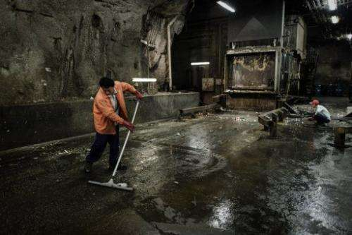 Workers at an underground cavern where waste is prepared prior to being transferred to landfills, on March 6, 2012