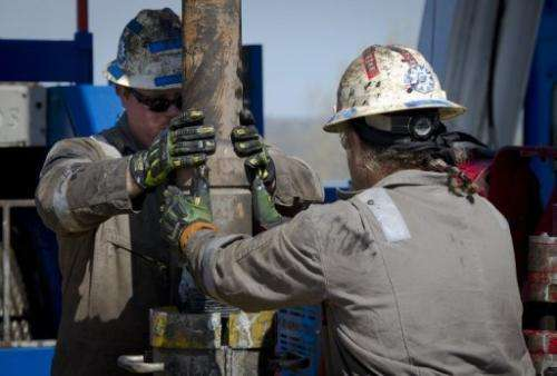 Workers change pipes at a rig exploring the Marcellus Shale outside the town of Waynesburg in Pennsylvania