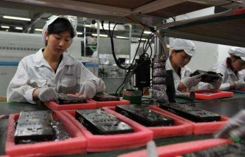 Workers inspect motherboards on a factory line at the Foxconn plant in Shenzen, southern China on May 26, 2010