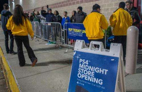 Yellow-clad customer service representatives brief camped-out shoppers as they wait in line to purchase the new PlayStation 4 (P