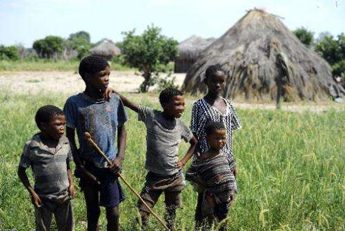 Young Kalahari Bushmen pose for a photograph outside a traditional hut on February 18 , 2012 in Molapo, in the centre of the Kal