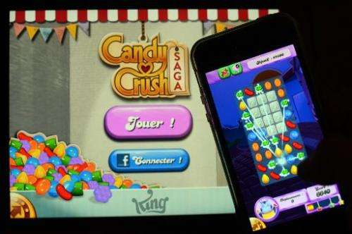 A man plays Candy Crush Saga on his iPhone on January 25, 2014