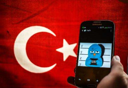 A picture representing a mugshot of the twitter bird is seen on a smart phone with a Turkish flag in Istanbul on March 26, 2014