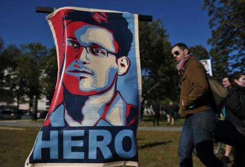 """A picture taken on October 26, 2013 shows a portrait of Edward Snowden declaring him a """"hero"""" during a protest against"""