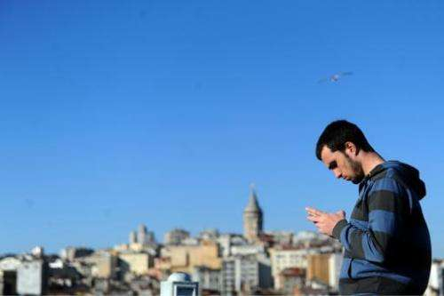A Turkish man uses his smartphone in the Eminonu district of Istanbul, on March 21, 2014