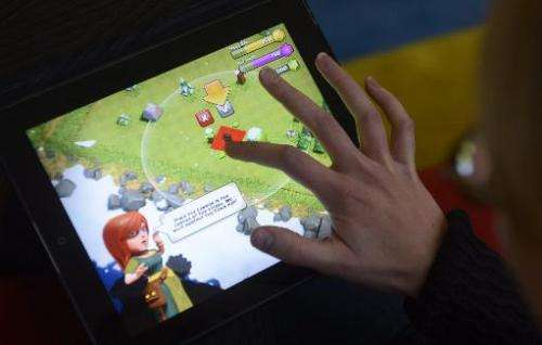 File photo shows a woman playing the 'Clash of Clans' game made by Finnish firm Supercell on a tablet computer oin Helsinki, on