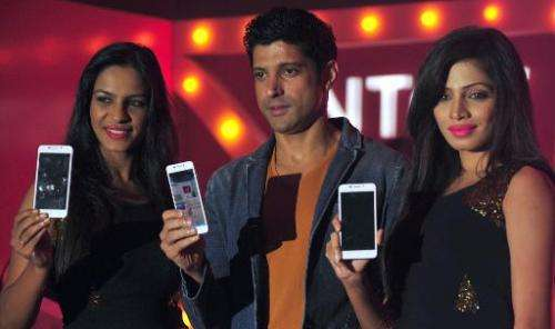 Indian Bollywood actor-director Farhan Akhtar (centre) poses with models holding the new Intex Aqua i7 phone at the  launch even