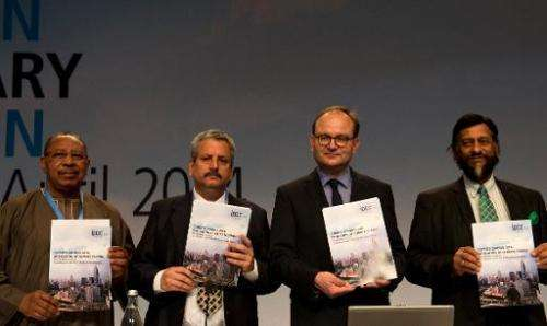 "Intergovernmental Panel on Climate Change (IPCC)pose with a copy of the IPCC report ""Climate Change 2014, Mitigation of Cli"