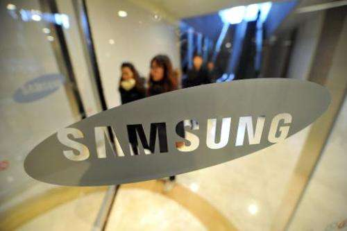 Pedestrians walk past a logo of Samsung Electronics at the company's headquarters in Seoul on January 24, 2014