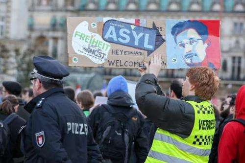 Protestors hold up placards featuring a picture of former NSA contractor Edward Snowden during a march against the spying method