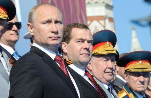 Russia's President Vladimir Putin (L) and Prime Minister Dmitry Medvedev (2nd L) attend a Victory Day parade at the Red Square i