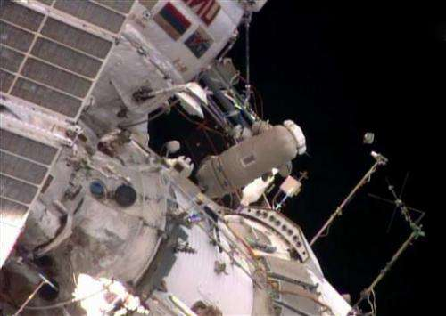 Spacewalking astronauts release baby satellite (Update)