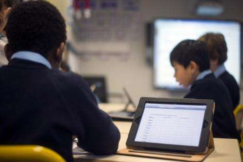 Students use tablets at a school in Paris on December 3, 2012