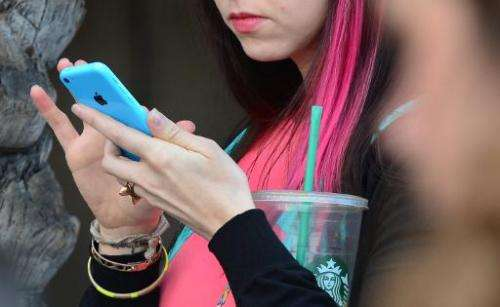 Women use their cellphones on January 7, 2014 in Los Angeles, California