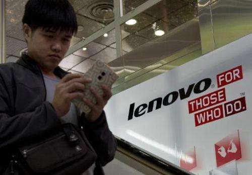 A man walks past an advertising billboard for Chinese technology giant Lenovo in Hong Kong on February 4, 2014