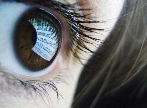 A picture shows binary code reflected from a computer screen in a woman's eye