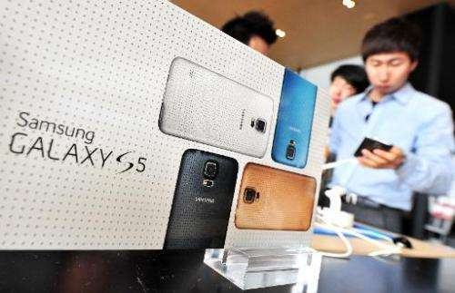 A South Korean customer looks at Samsung's Galaxy S5 smartphone at a mobile phone shop in Seoul on March 27, 2014