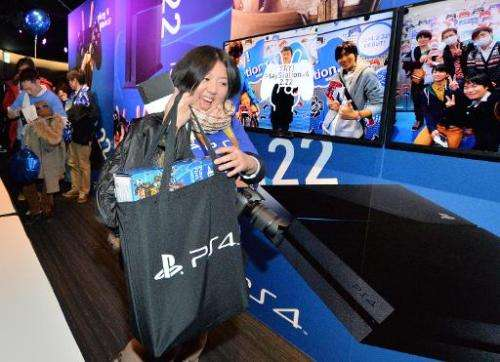A woman carries a newly-purchased Sony PlayStation 4 video game console at the Sony building in the Ginza district of Tokyo on F