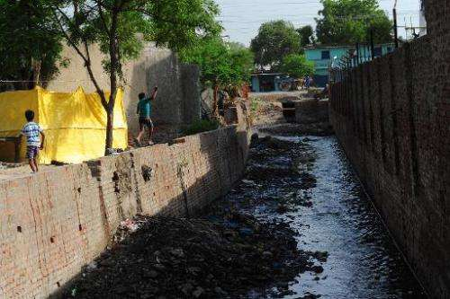 Children play by a polluted canal that runs into the river Ganges in the Jajmau area of Kanpur on June 26, 2014