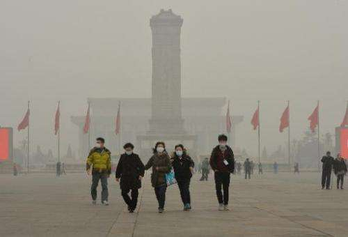 Chinese tourists wear facemasks during a visit to Tiananmen Square as heavy air pollution shrouds Beijing on February 26, 2014