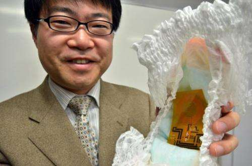 University of Tokyo professor Takao Someya pictured with the world's first disposable wireless organic sensor embedded in a diap