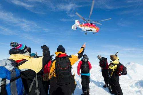 A helicopter from the nearby Chinese icebreaker Xue Long hovers above passengers from the Russian ship MV Akademik Shokalskiy as