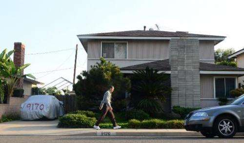 A man walks past the reported home of Satoshi Nakamoto in Temple City, east of Los Angeles, California on March 6, 2014