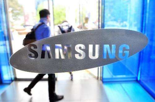 A visitor walks past a logo of Samsung Electronics at the company's headquarters in Seoul on April 29, 2014