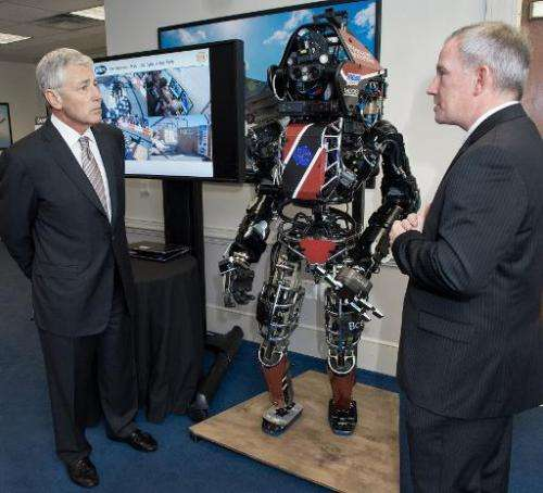 US Secretary of Defense Chuck Hagel (L) is shown the Atlas robot by Brad Tousley, head of DARPA's Tactical Technology Office, at
