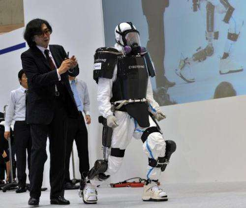 University of Tsukuba professor and president of Cyberdyne Yoshiyuki Sankai (L) unveils a robot suit at the Japan Robot Week exh