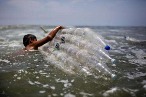A boy gets into the sea with a surfboard made from plastic bottles as part of an environmental recyclying project, in Lima, on F