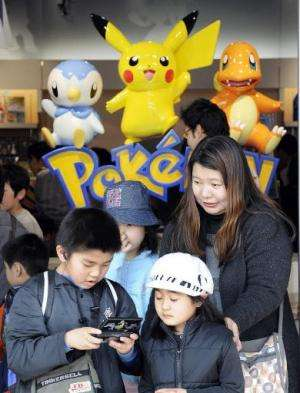 A boy plays Nintendo's portable video game 'DS' in front of display of game character Pokemon, at a shop in Tokyo, on April 4, 2