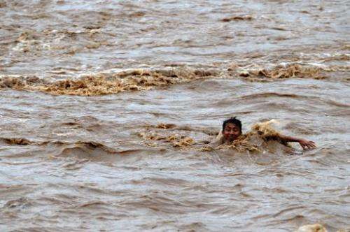 A boy tries to cross the overflowed Huiza River in La Libertad, 40 km south of San Salvador, on May 30, 2010 amid tropical storm