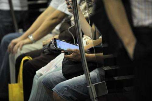 A commuter is seen using his smartphone while travelling on a Mass Rapid Transit train in Singapore, on April 30, 2014