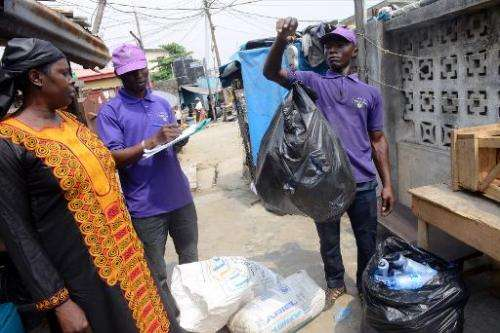 A customer (L) watches as staff of 'Wecycler' weigh and record recyclable goods, collected from her in Surulere district of Lago