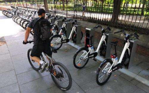 A cyclist looks at electric bicycles parked at a bike-sharing station in Madrid on June 23, 2014