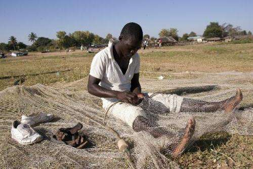A fisherman fixes a net on the shores of Lake Malawi, near the Makawa Fishing Village in the district of Mangochi on May 18, 201