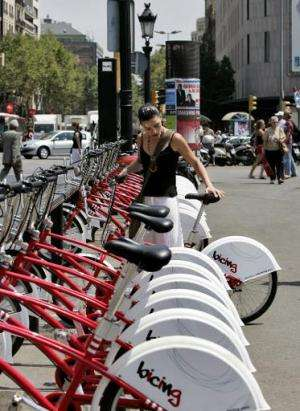 "A girl takes a ""Bicing"" bike - part of a shared bicycle scheme - for a ride on July 18, 2007, in Barcelona"