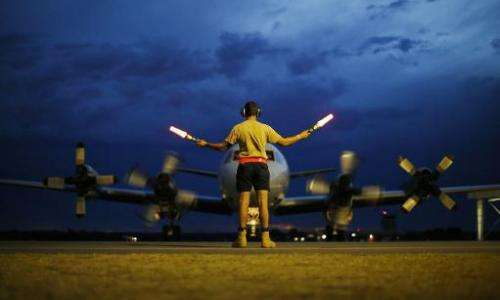A ground controller guides a Royal Australian Air Force AP-3C Orion after a search operation for the flight MH370 over the India