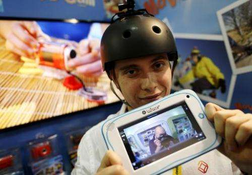 Alexandra Delage from Lexibook holds a tablet connected wirelessly to a mini camera attached to a helmet during the Toy Fair at