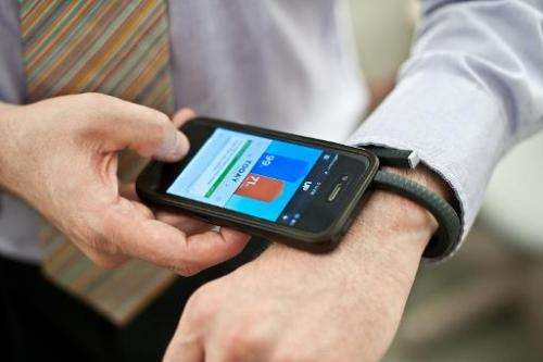 A man is seen using a Jawbone UP fitness wristband and its smartphone application, in Washington, DC, on July 16, 2013