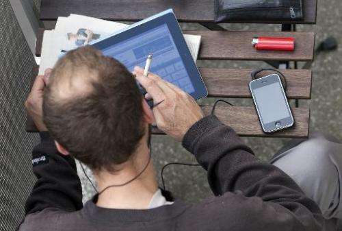 A man is seen working on an iPad, on a balcony in Berlin, Germany, on June 23, 2011