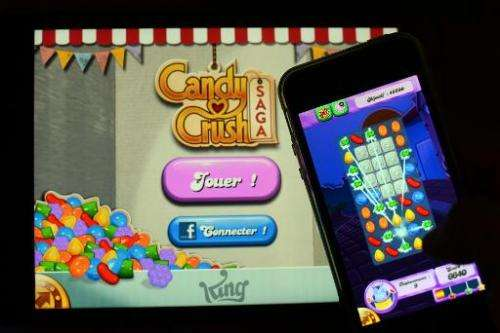 A man plays Candy Crush Saga video game on his mobile phone