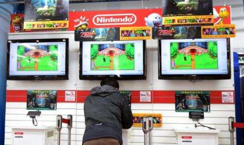 A man plays Nintendo's portable video game console at an electronic shop in Tokyo on January 17, 2014
