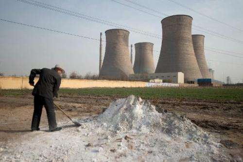 A man shovels earth in a field outside a power plant in Xingtai, southern Hebei province, on March 10, 2013