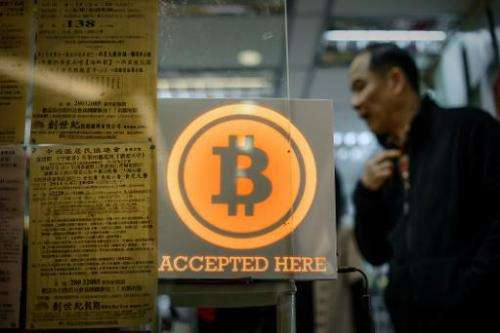 A man walks out of a shop displaying a bitcoin sign during the opening ceremony of the first bitcoin retail shop in Hong Kong on
