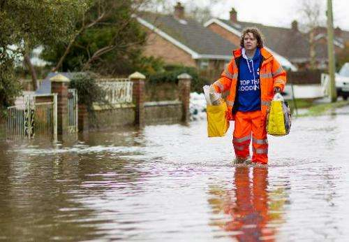 A man walks through flooded streets in the village of Moorland in Somerset, south-west England, on February 6, 2014