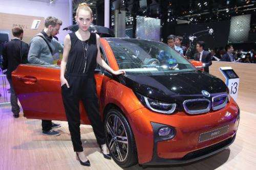 A model poses by an i3, a BMW electric car, on display at the Beijing Automotive Exhibition on April 20, 2014