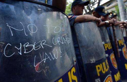 An anti-cybercrime law slogan is wriiten on a shield of a policeman during a protest near the supreme court in Manila on January