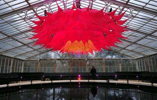 An employee poses behind a giant Lotus Flower installation in the Water Lilly House at Kew Royal Botanical Gardens in south west